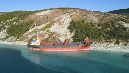Aerial top view of an empty, red barge moored near the beautiful blue sea shore. Big Industrial ship standing near the hill with green trees