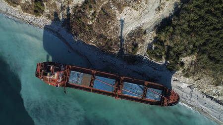 Aerial top view of red industrial ship with people on board doing sailor work moored near sea shore. Shot. Big barge on the coastline near forested slope and people walking around.