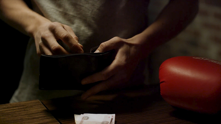 Close up of man hands holding an open leather wallet with a few coins inside over a old wooden table with paper money lying on it. Male putting coins on banknotes in dark room, russian rubles