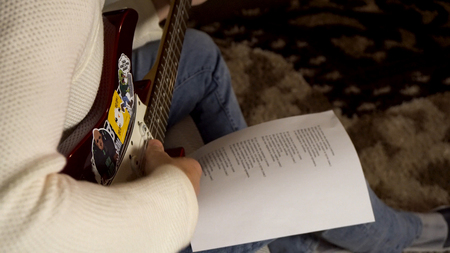 Musician playing electric guitar and looking at paper with printed song words lying on his knee. Man guitarist in creating song process. 스톡 콘텐츠
