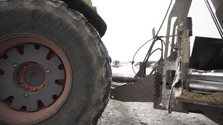 Close up for moving tractor with trailer at the farm in winter, agriculture concept. Footage. Agricultural machinery, tractor driving on snow.