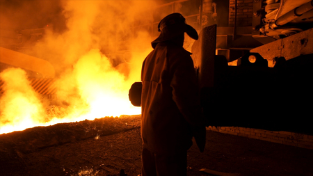 Metallurgist worker in protective uniform at the steel plant controlling hot molten metal pouring process. Man working in heavy industry.