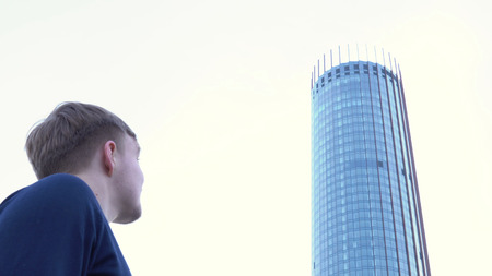 Rear view of man looking at glass building. Media. Man stands and looks at glass facade of modern office building Banco de Imagens