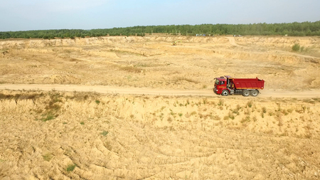 Dump truck driving on rural road. Scene. Top view of truck rides, leaving plumes of dust in dirt road in countryside on background of excavator career