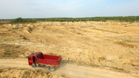 Dump truck driving on rural road. Scene. Top view of truck rides, leaving plumes of dust in dirt road in countryside on background of excavator career Banque d'images