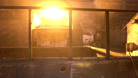 Metal steel worker in special uniform passing through metallurgical shops with bif metal furnace. Stock footage. Working at metal steel plant.