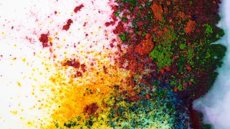 Top view of dry green, yellow and red inks floating in white milky substance. Media. Beautiful iridescent background with colorful paints mixed with white colored liquid.