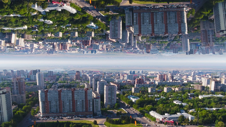 Aerial view of the city in a summer day with nature in the middle of the city, mirror horizon effect. Media. Aerial city view with crossroads, roads, houses, parks and river bridge, inception theme. Banco de Imagens