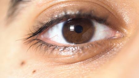 Cerrar imagen de hermosos ojos marrones de un hombre joven, concepto de detalle de cara. Medios de comunicación. La pupila del ojo masculino se estrecha y se ensancha.