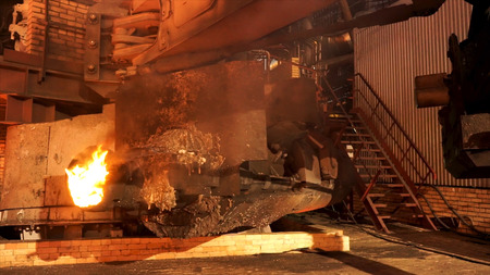 Close up for the equipment at the metallurgical plant with burning furnace melting steel. Stock footage. Shop at the metal pipes production factory. Фото со стока