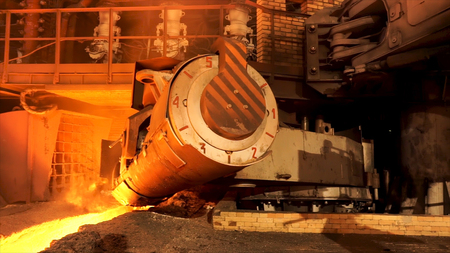 Close up for aluminum melting furnace in a foundry moving backwards, heavy metallurgy concept. Stock footage. Equipment of liquid and solid metal factory production. Imagens