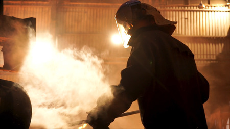 Steel worker removing slag from the electric induction crucible melting furnace at the metallurgical plant, hard work conceprt. Stock footage. Man in protective mask and uniform working with a poker.