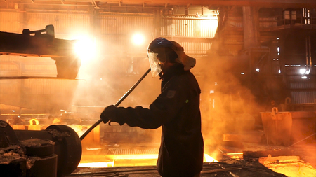 Vista lateral del perator elimina los desechos de la tubería del horno en la planta de fundición de hierro. Metrajes. Trabajador de hombre en traje resistente al calor que limpia el horno de alta temperatura. Foto de archivo