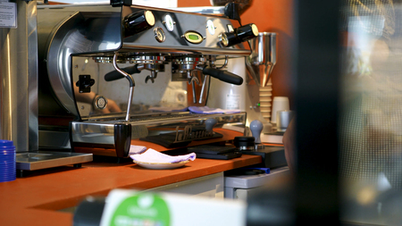 Barista at professional coffee machine in coffee shop. Art. Barista washes and wipes espresso machine before making cup of coffee in cafe. Imagens