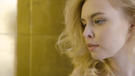 Beautiful blonde woman face close up. Action. Close-up of the face of a beautiful blonde woman in the sun Imagens - 124891335