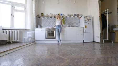 Relaxed sexy blonde posing on kitchen in morning. Action. Sexy young blonde woman in the kitchen at home