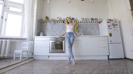 Relaxed sexy blonde posing on kitchen in morning. Action. Sexy young blonde woman in the kitchen at home Imagens - 124891343