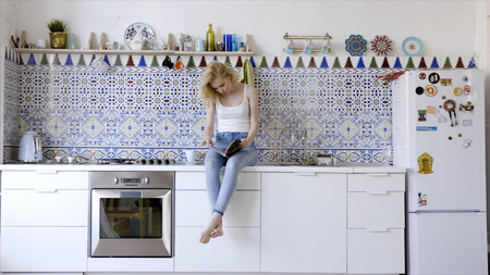 Looking through magazine in the morning. Action. Beautiful cheerful young woman reading magazine while sitting at the kitchen at home