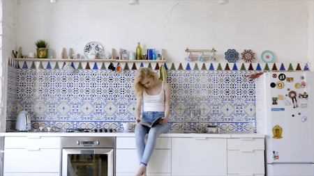 Looking through magazine in the morning. Action. Beautiful cheerful young woman reading magazine while sitting at the kitchen at home Imagens - 124891432