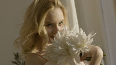 Young blonde woman with flowers in her hands in the sun. Action. Young beautiful woman in sunlight at home with flowers