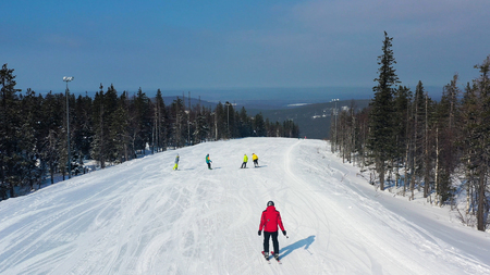 Modern ski resort in pine forest aeria, view from above. Footage. Young group of people snowboarding and skiing down the snowy slope.