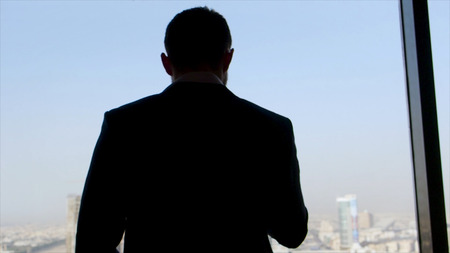 Rear view of a businessman in the suit standing with his smartphone in hand, looking out of the window. Stock. Company leader at the window, view from skyscraper to the city. Imagens