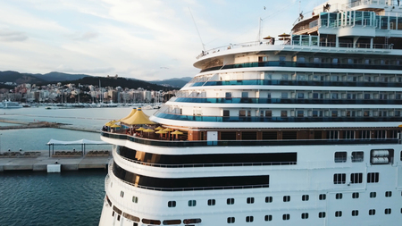 Close up of the cruise liner back with cabins and big sun umbrellas on board, travel and resort concept. Stock. Cruise ship at the sea port with white yachts, mountain and coastal city.
