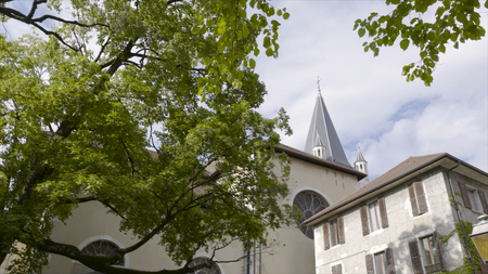 Church and green tree in Europe. Action. The tower of the parish church behind green trees in early spring Stok Fotoğraf
