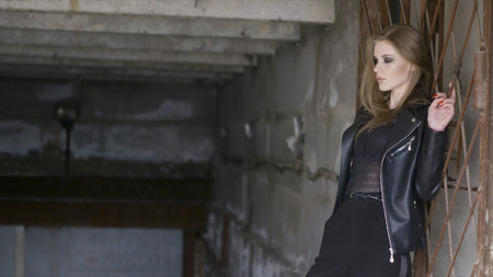 Young beautiful woman in black leather jacket in urban environment. Action. Stylish beautiful model in the city
