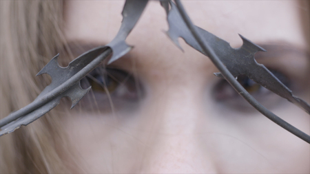 Close-up of a young womans eyes through barbed wire. Action. Beauty fashion concept