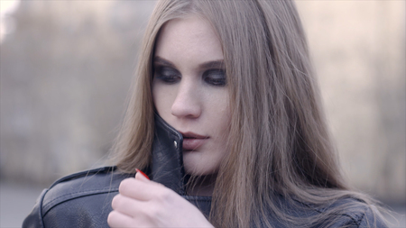 Stylish woman looking at camera outdoors in the street. Action. The face of a satisfied young woman in the city Imagens