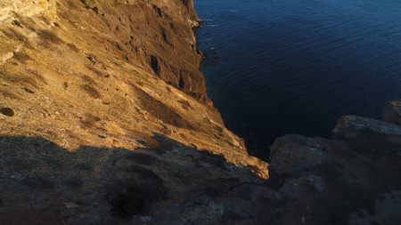 Aerial view of rocky calm ocean coast at the sunset. Shot. Beautiful view from the cliff edge on the ocean surface.