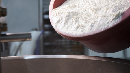 Close up for white flour being put to the iron bowl at the bakery, bread products concept. Stock footage. White flour falling down from the plastic bowl.