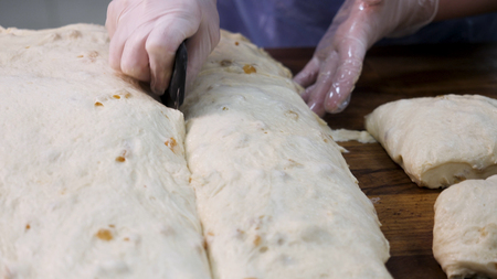 Close up for baker cutting dough into pieces before cooking and weighing them at the bakery. Stock footage. Woman making bread pieces from raw pastry an putting in on the scale. Imagens