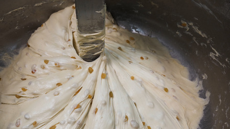 Close up for the prosess of mixing pastry with raisins in metal bowl, nutritious food concept. Stock footage. Raw dough mixing process at the factory. Imagens - 124087487