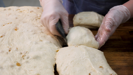 Close up for woman in cooking gloves cutting the dough into pieces with a special knife. Stock footage. Women hands cut the raw kneaded dough into pieces on wooden board. Imagens