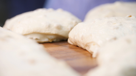 Close up view for raw pieces of pastry lying on the wooden board on the table. Stock footage. Traditional delicious pastry pieces with raisins ready for baking. Imagens - 124087556