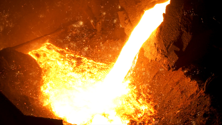 Fusion du métal dans la fonderie de l'aciérie. Images d'archives. Gros plan sur l'acier chaud versé du four avec de nombreux sparcles, industrie du fer.