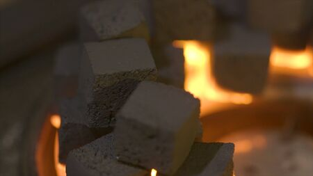 Close-up of burning charcoal cubes. Action. Cubes of embers burning in bowl for smoking hookah. Combustion of small flame of yellow fire burning pieces of coal