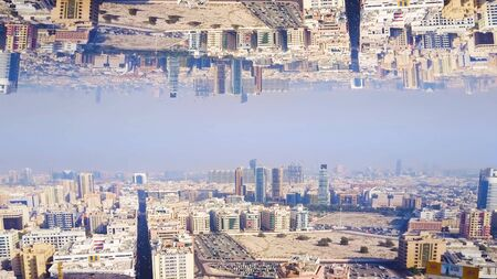 Modern city with mirror effect. Stock footage. Abstract animation with effect of parallel reality of reflected metropolis. Top view of city panorama mirrored from above like parallel worlds. Imagens