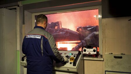 Back view of a worker in uniform standing in the control room of the steel making workshop. Stock footage. Blast furnace control panel, heavy metallurgy concept.