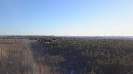 Quadcopter falls to ground. Clip. Top view of quadcopter lost communication and begin to fall to ground. Quadcopter in air on background of forest with horizon of blue sky