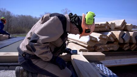 Working makes measurements with special device. Clip. Builder in shape and helmet makes measurements of wooden board by measuring device on construction site