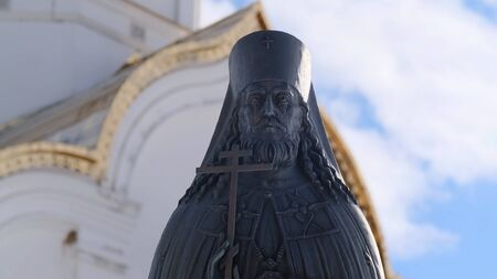 Metal statue of priest on background of church. Stock footage. Beautiful statue of sacred minister with clear details standing in front of church against blue sky. Concept of religion