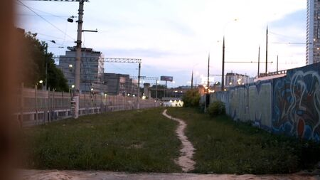 View of trail next to railway. Stock footage. Empty footpath in grass next to railroad in suburbs. Evening lights of city on background of path at railway with concrete walls in graffiti