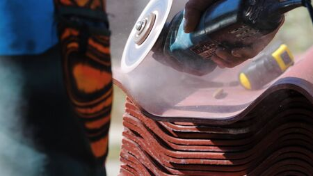 Man circular saw saws slate. Stock footage. Repair of the roof of slate. Circular saw in the hands of the builder. Construction tools
