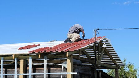 Man screws a screw into the roof. Stock footage. The professional worker works on installation of a roof of a roof by sheets of a metal tile and drills a screw with a drill Archivio Fotografico