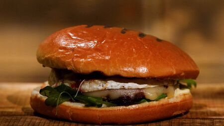 Tasty burger with beef, cheese and greens. Stock footage. Ready juicy Burger with cheese Imagens - 128054267