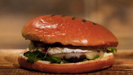 Tasty burger with beef, cheese and greens. Stock footage. Ready juicy Burger with cheese Imagens