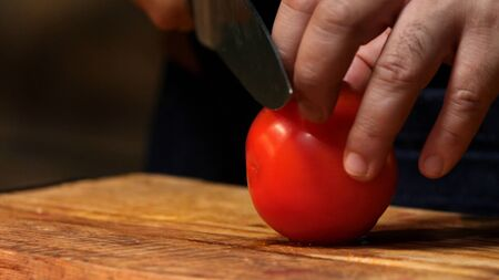 Cutting red tomato on wooden board. Stock footage. Chef cut tomato on a wooden Board